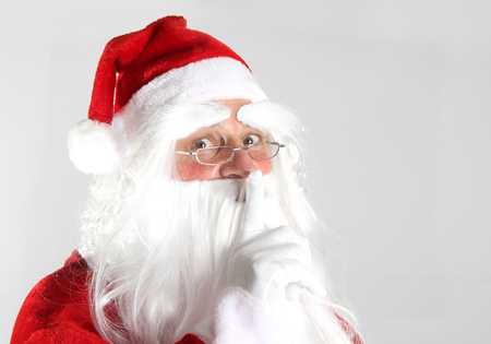 静かに保つために指を持っているクリスマスサンタクロース。 写真素材