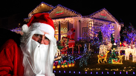 Santa Claus delivering Christmas presents to a house decorated with holiday lights.