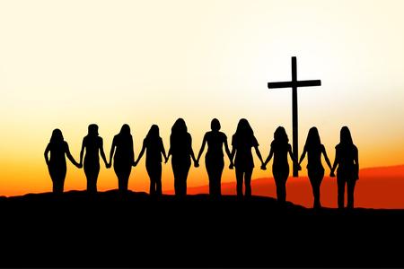 Sunset silhouette of 10 young women walking hand in hand toward a Christian Cross.  Foto de archivo