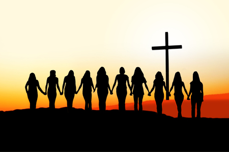 Sunset silhouette of 10 young women walking hand in hand toward a Christian Cross.  Stock Photo