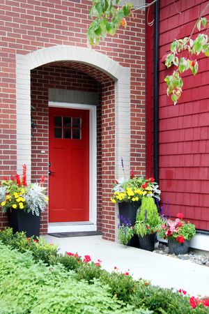 Red front door entrance with flowers on a brick house facade.