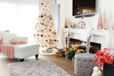 White contemporary Christmas tree. A plush loveseat sofa in the foreground with pink accents. Stockfoto