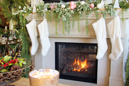 Knitted white Christmas stockings hanging on a fireplace mantle. Imagens - 112985878