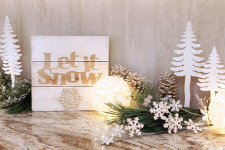 Wooden holiday let it snow sign with Christmas trees ornaments and bright lights. Stock Photo