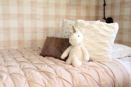 Eenhoorn knuffel leunend tegen bedkussens in een meisjeskamer.