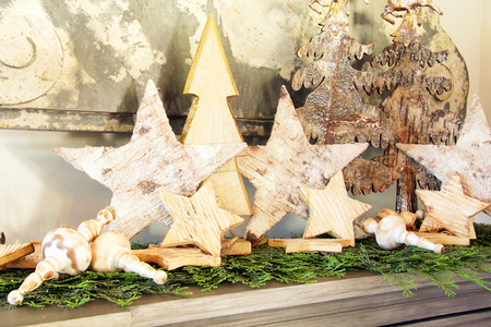 Vintage wooden Christmas stars display with greenery and wooden spinning top toys.