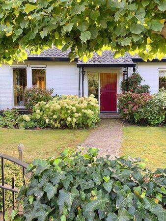 Nederlands charmant bakstenen huis met kleine poort en geplaveide tuinpad dat leidt naar rode voordeur. Stockfoto