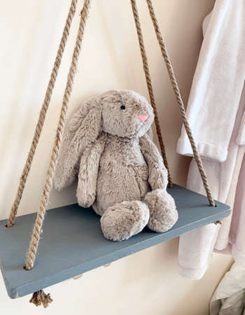 Stuffed animal on a swing in a child's bedroom. Cute cuddly bunny rabbit toy.