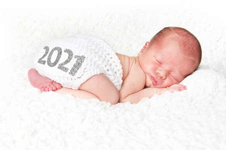 Newborn baby asleep on a white blanket with 2021on his knitted diaper cover. Happy New Year baby.
