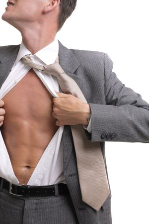 release! - young businessman dressed in suit, shirt and tie pulling his shirt open revealing well-built torso photo