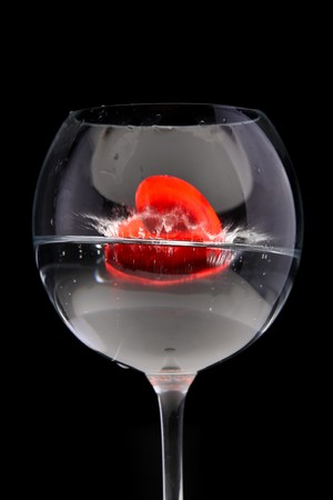 red jelly heart in wine glass on black background photo