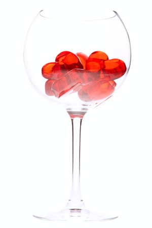 red jelly hearts in wine glass over white background photo