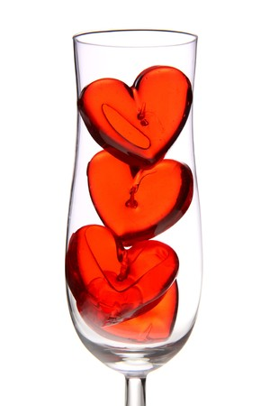 red jelly hearts in champagne glass over white background photo