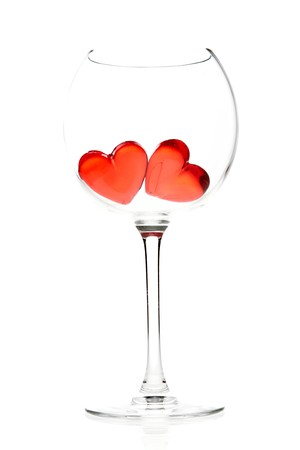 two red jelly hearts in wine glass over white background