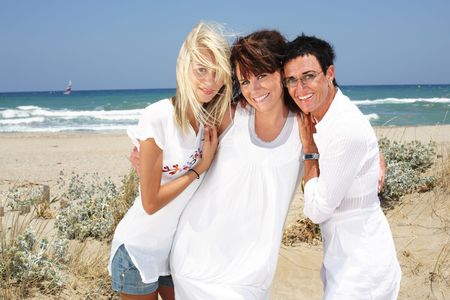 happy mother and daughters having fun on the beach photo