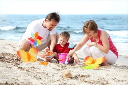 family holidays: young happy family on the beach