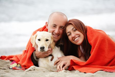 valentines dog: attractive romantic couple with a dog having fun on the beach