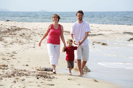 young happy family taking a walk along the beach photo