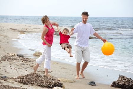 young happy family playing on the beach Stock Photo - 4863089