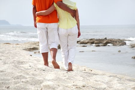 mature female: mature couple in love walking along the beach Stock Photo