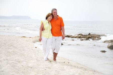 beautiful mature couple walking along the beach Stock Photo