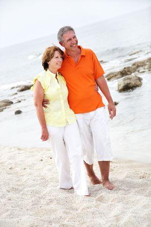 beautiful mature couple walking along the beach photo