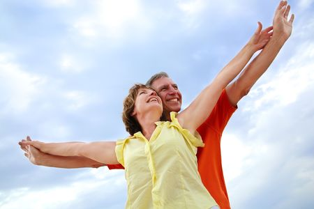 beautiful mature couple standing with arms outstretched Stock Photo - 4915125