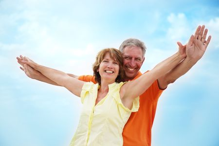 Mature couple with arms outstretched photo