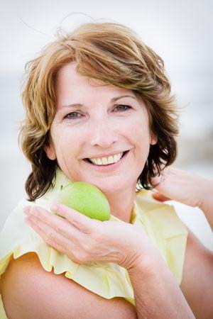 mujeres ancianas: Close-up retrato de feliz y hermosa mujer madura sosteniendo una manzana