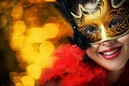 Beautiful young woman in carnival mask over gold background photo