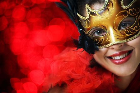 Beautiful young woman in carnival mask over red background photo