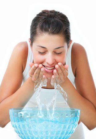 Beautiful young woman washing her face photo
