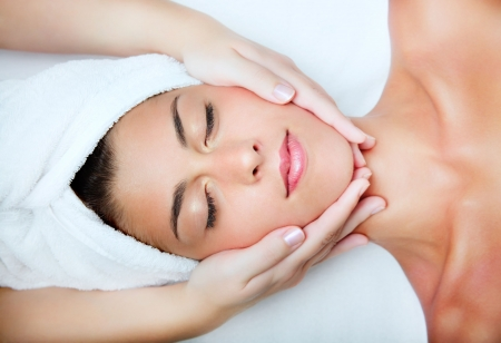 Beautiful young woman receiving facial massage photo
