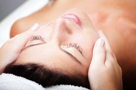 Close-up of a beautiful young woman receiving facial massage photo