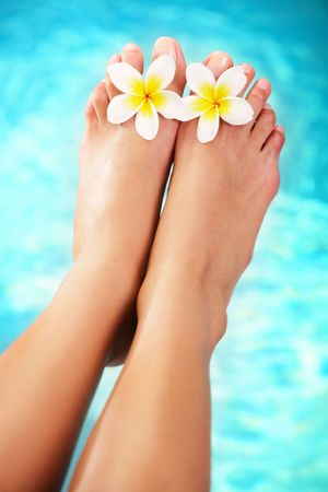 Beautiful pedicured female feet and tropical flowers Stock Photo - 6147019