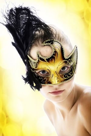 costume ball: Beautiful young woman in carnival mask. Isolated on abstract background.