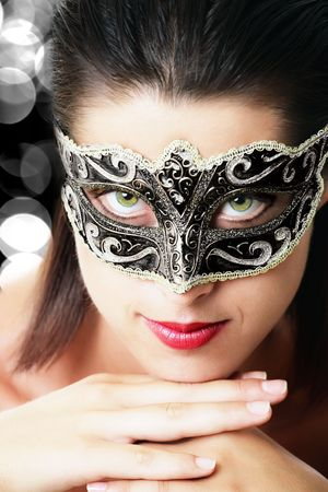 Beautiful young woman in carnival mask. Isolated on abstract background. photo