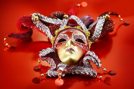 drama mask: Ornate carnival mask over red metallic background.