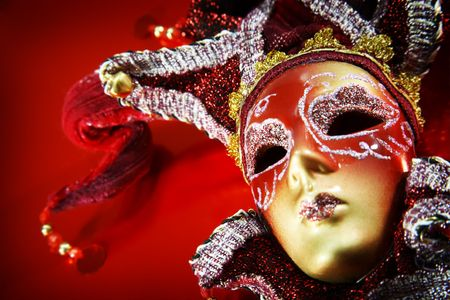 Ornate carnival mask over red metallic background.