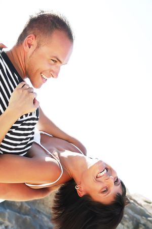 Smiling young couple having fun at the beach photo