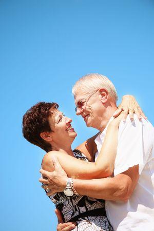 Mature couple on blue sky background photo