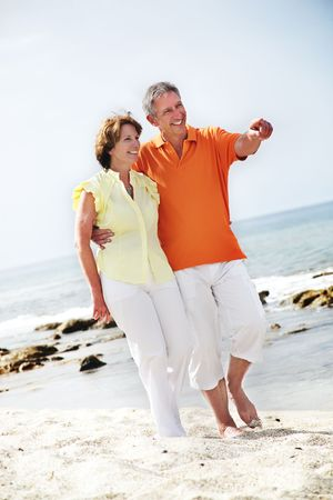 middle adult: Happy mature couple walking along the beach.