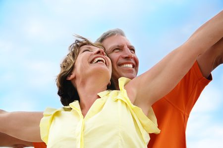 mid adults: Happy mature couple standing with arms outstretched.