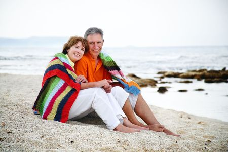 Happy mature couple sitting on the beach.  photo