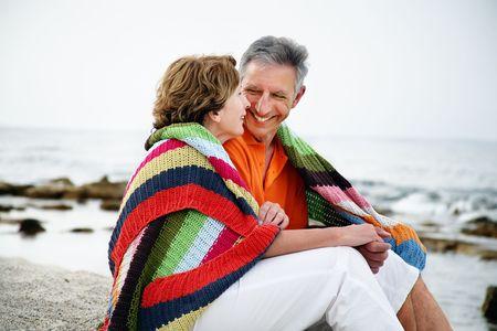 Happy mature couple sitting on the beach. Stock Photo - 6428664