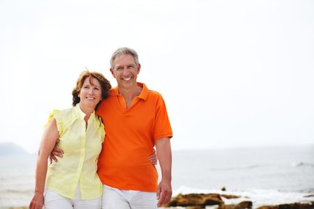mid adult   female: Happy mature couple walking along the beach.