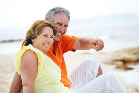 pareja madura feliz: Feliz pareja madura sentado en la playa.