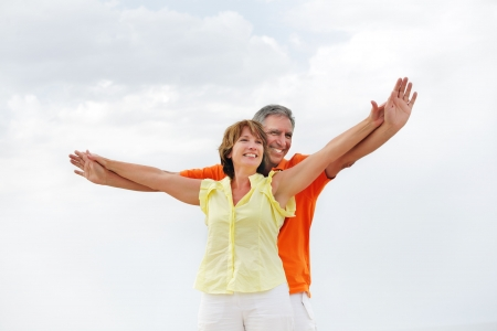 middle adult: Happy mature couple standing with arms outstretched.