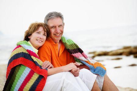 mid life: Happy mature couple sitting on the beach.  Stock Photo