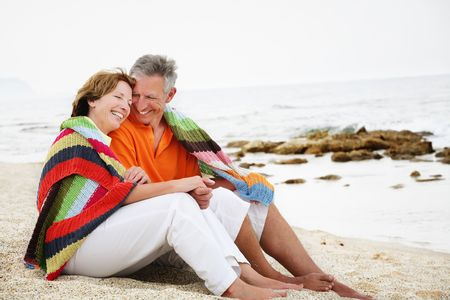 the old days: Happy mature couple sitting on the beach.  Stock Photo